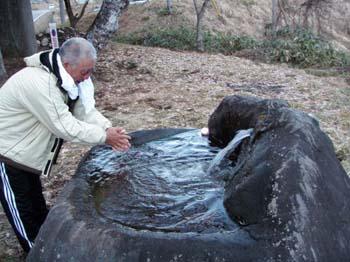 栗巣川沿いのお宮で手を洗う浅野さん