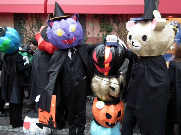 ネコと熊がハロウィンの飾りの前でポーズ