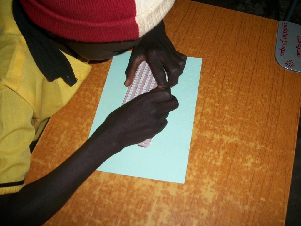 点字板で点字を学ぶ子ども