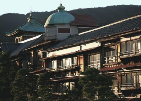 夕陽を浴びる川岸の旅館