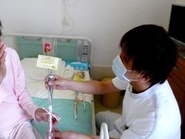 病室でお花を手渡す看護師
