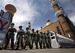 9日、中国新疆ウイグル自治区ウルムチの中心部にある、モスクの入り口で警備に当たる中国の兵士(ロイター)