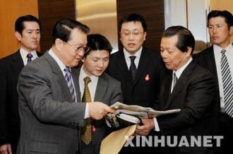 日本のメディア各社の代表を招いた李長春(左)。右は朝日新聞社の船橋洋