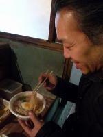 屋台ラーメンを美味しそうに食べる村山義光氏