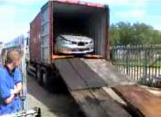 トラックのコンテナから引き出され始めたインプレッサの写真