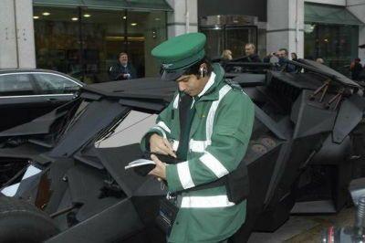 バットモービルの駐禁キップを切ろうとしている駐車監視員の写真