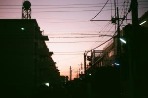 マンションの奥に落ちる太陽