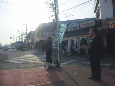 マイクを握る清沢議員とチラシを配る駒崎議員