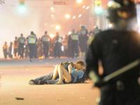 カナダで暴動が起こっている中、路上でキスをするカップルの写真