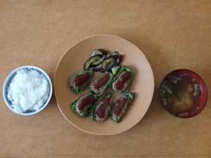 皿に盛り付けたピーマンの肉詰め。付け合せには茄子を炒めた。