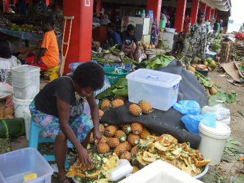 マーケットでパイナップルの皮をむく女性